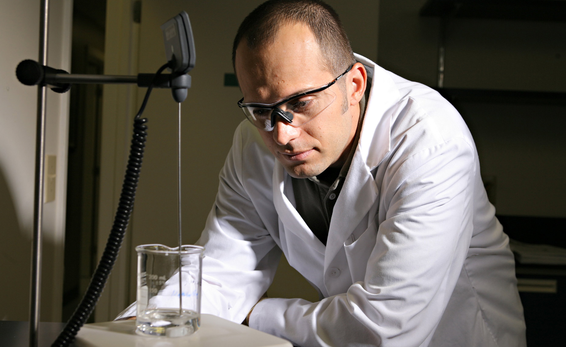 Medical technologist with sample beaker