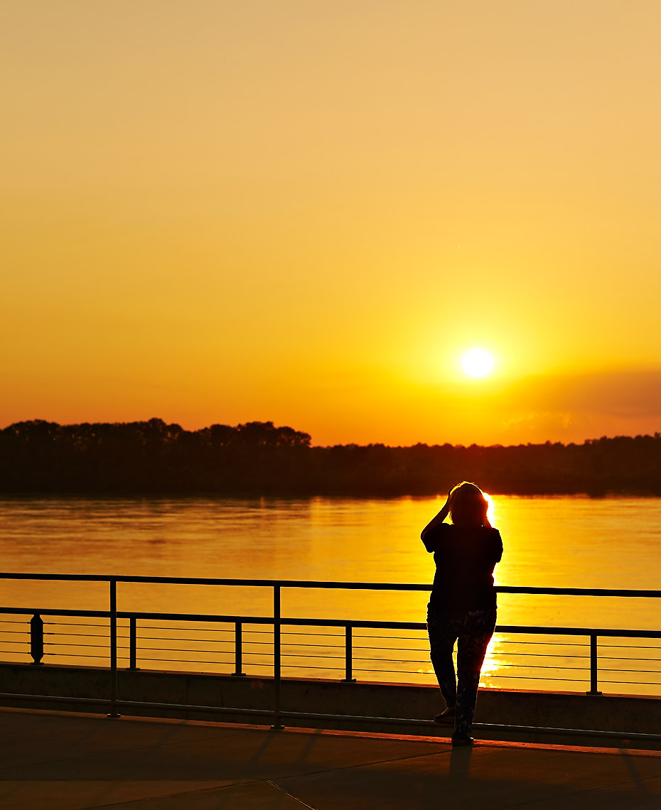 Photographer capturing sunset on the Mississippi River from Beale Street Landing in Memphis TN