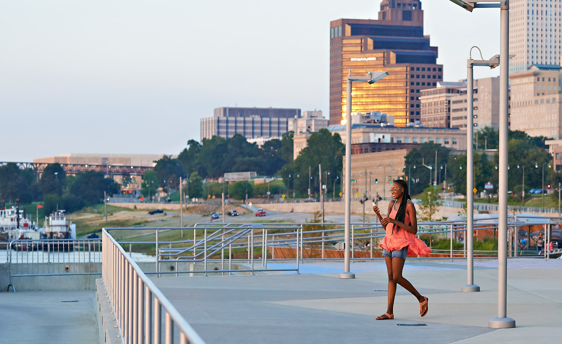 A young lady walks towards the Mississippi River from Beale Street Landing
